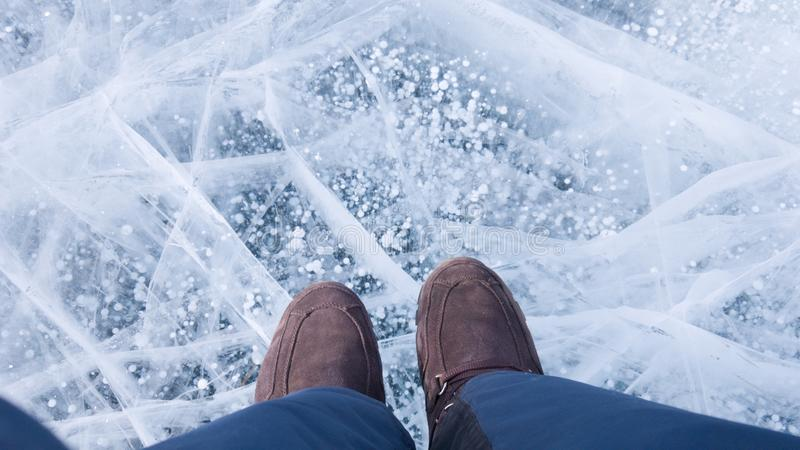 Sports Hiking warm shoes on the feet of the traveler. The tourist stands on the beautiful ice with bubbles on lake Baikal.  royalty free stock photos