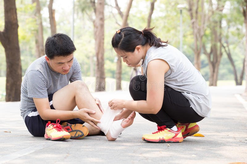 Sports injury. Man with twisted sprained knee and getting help f. Sports injury. Man with twisted sprained ankle and getting help from women bandaged ankle in royalty free stock images