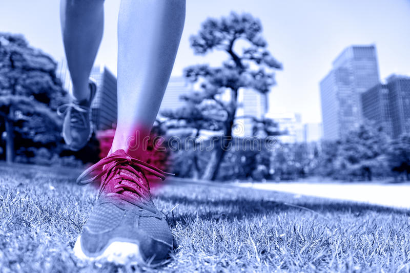 Sports injury - runner feet with ankle pain. Closeup of running shoes landing on soft grass with red circle showing hurting joints and ligaments caused by a royalty free stock images