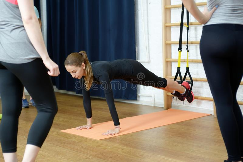Sports instructor shows how to do exercise on suspension rope trx group of girls.  stock image