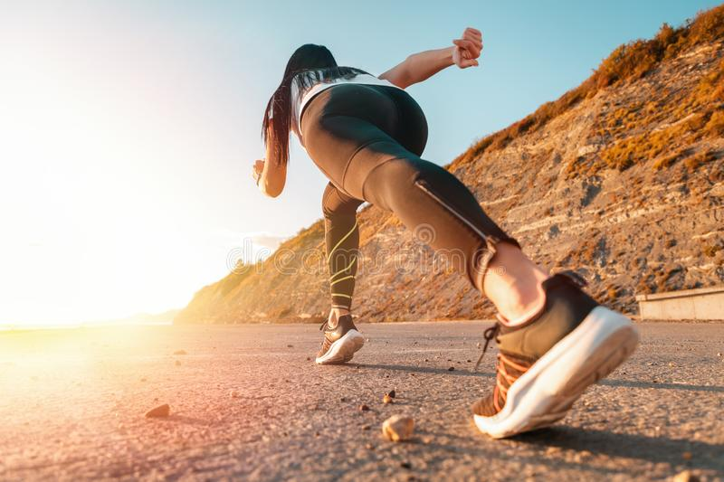 Sports and Jogging along the sea. The woman stands ready to run. In the background, the mountain and the sun. Bottom view.  stock photography