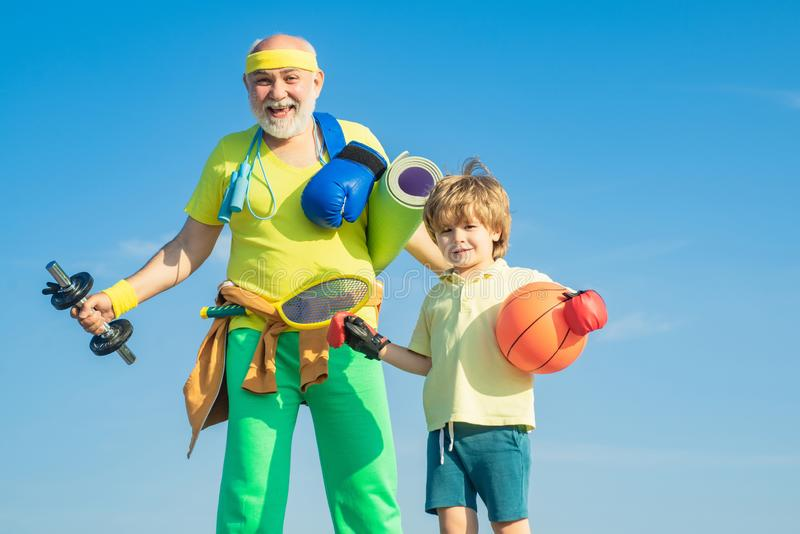 Sports for kids. Father and son sporting - family time together. Senior man and cute little boy exercising on blue sky. Background - isolated stock photo