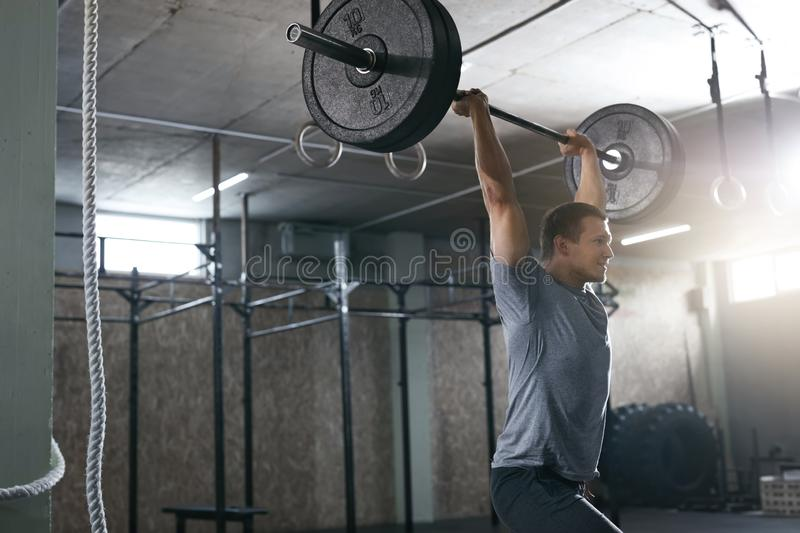 Sports Man Lifting Barbell Row At Workout Gym stock photography