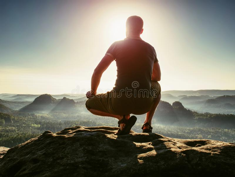 Sports man in outoor clothes and boots walking on rocky peak stock photos