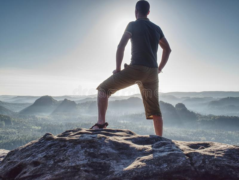Sports man in outoor clothes and boots walking on rocky peak stock images