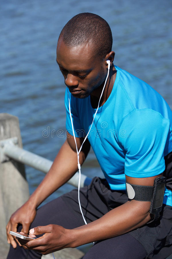 Sports man sitting outside listening to music on mobile phone royalty free stock photos