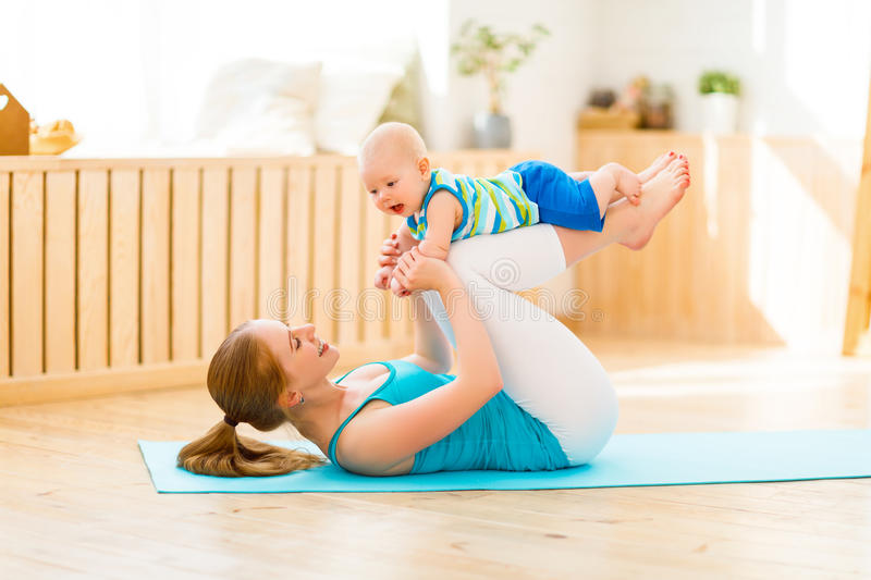 Sports mother is engaged in fitness and yoga with baby at home. Sports mother is engaged in fitness and yoga with a baby at home