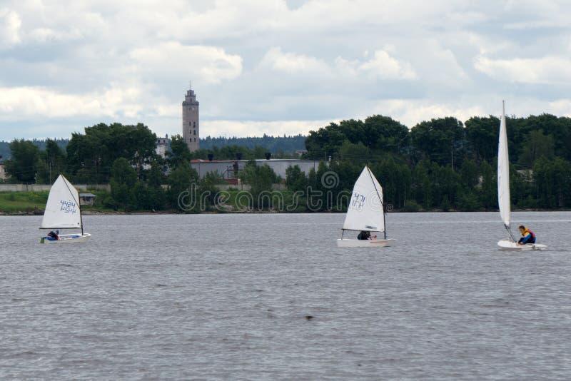 Sports naviguant dans un bon nombre de petits bateaux blancs sur le lac photos stock