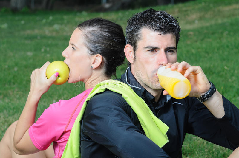 Sports Nutrition. Couple of athletes taking a break, eating an apple and drinking isotonic drink stock photo