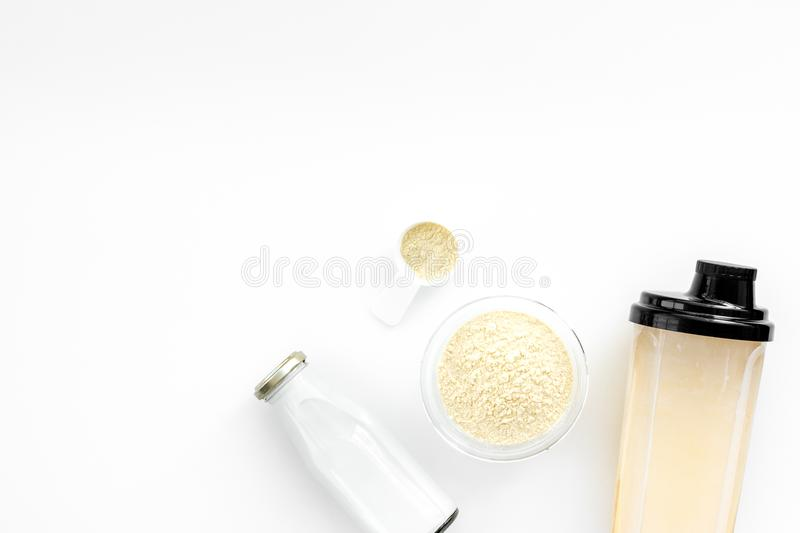 Sports nutrition. Scoop of protein near shaker on white background top view copy space royalty free stock images