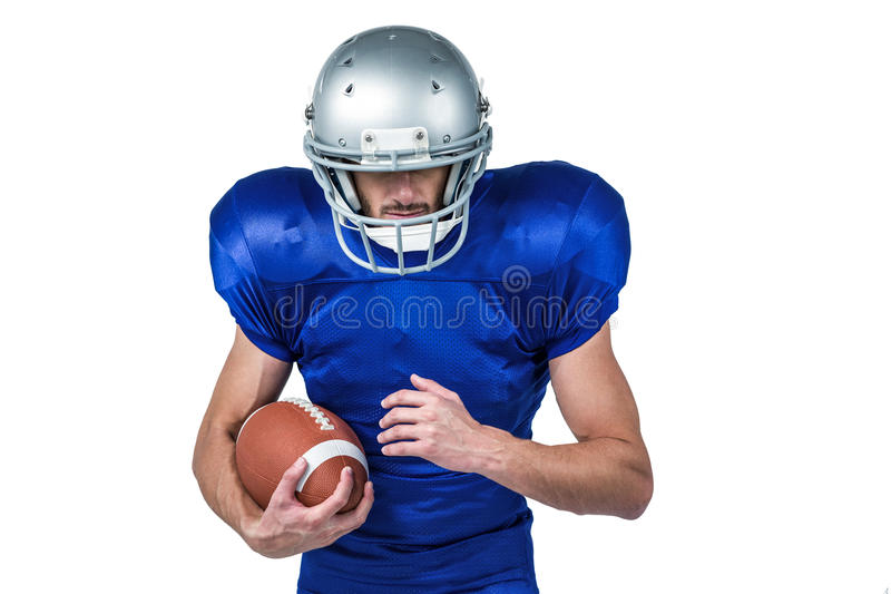 Sports player wearing helmet while holding ball. Against white background royalty free stock photography