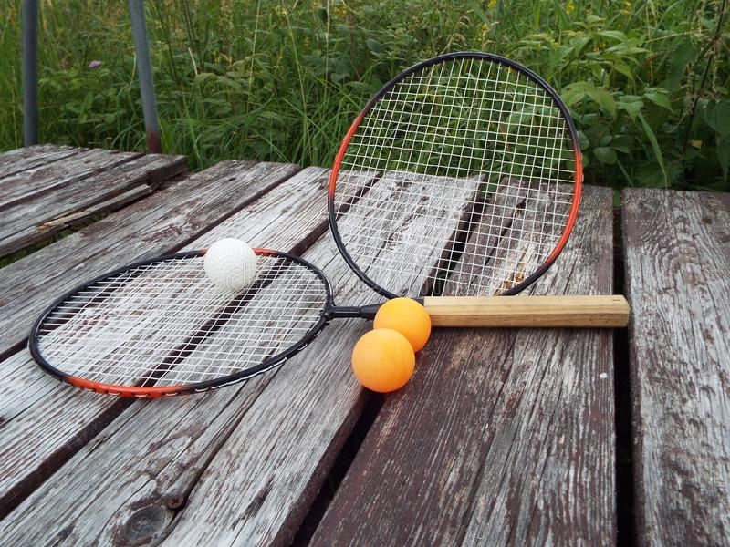 Sports rackets and tennis balls on a wooden background in nature. royalty free stock photography