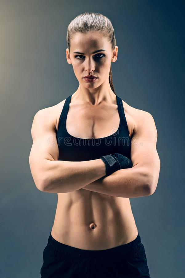 Muscular sporty lady posing with arms crossed royalty free stock photo