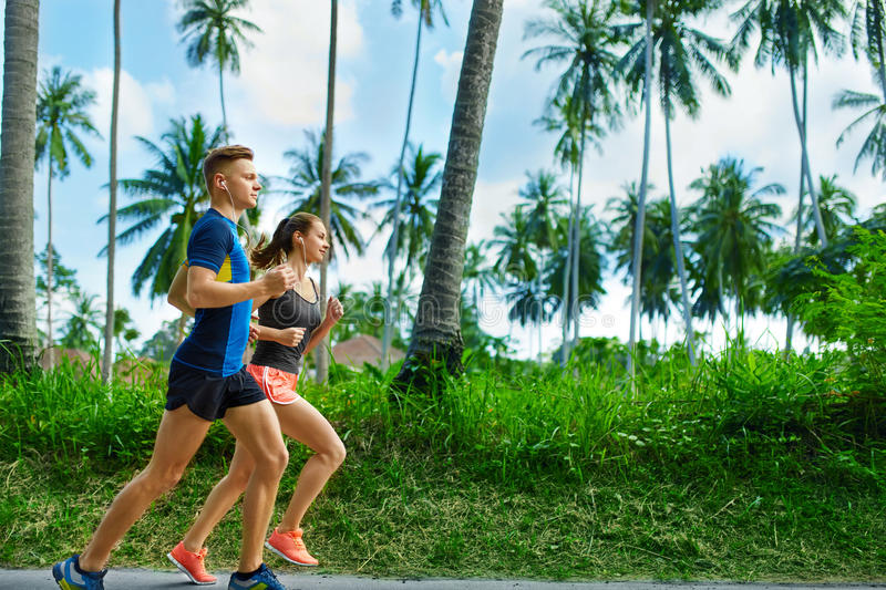 Sports. Runner Couple Running, Jogging On Road. Fitness, Healthy. Sports. Sporty Runner Couple Running On Sidewalk, Training For Marathon. Athletic Woman And Fit royalty free stock photography