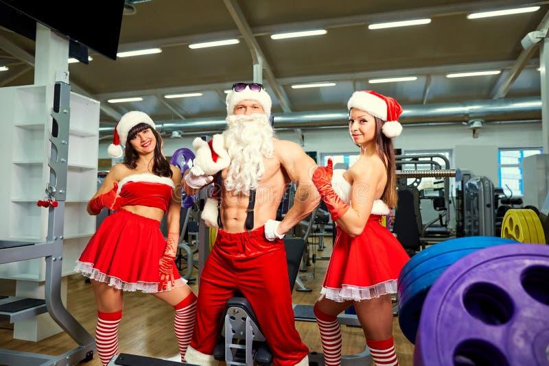 Sports Santa Claus avec des filles dans des costumes du ` s de Santa dans le gymnase photographie stock libre de droits