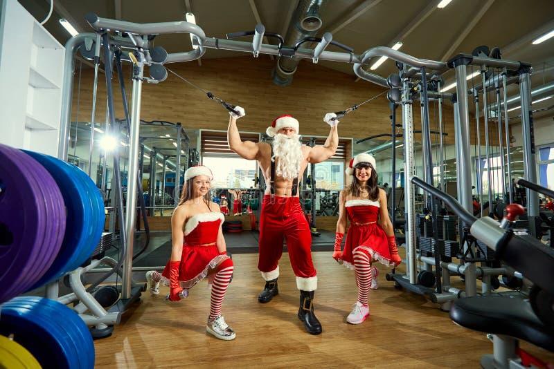 Sports Santa Claus avec des filles dans des costumes du ` s de Santa dans le gymnase images libres de droits