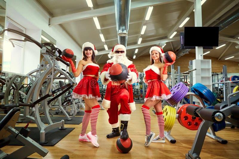 Sports Santa Claus avec des filles dans des costumes du ` s de Santa dans le gymnase dessus photographie stock libre de droits