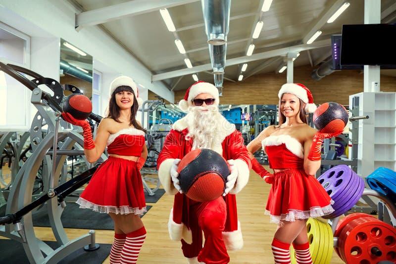 Sports Santa Claus avec des filles dans des costumes du ` s de Santa dans le gymnase dessus photographie stock