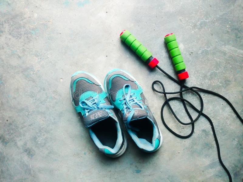 Sports shoe and skipping rope. High angle view of blue shoes and skipping rope on the ground stock photos