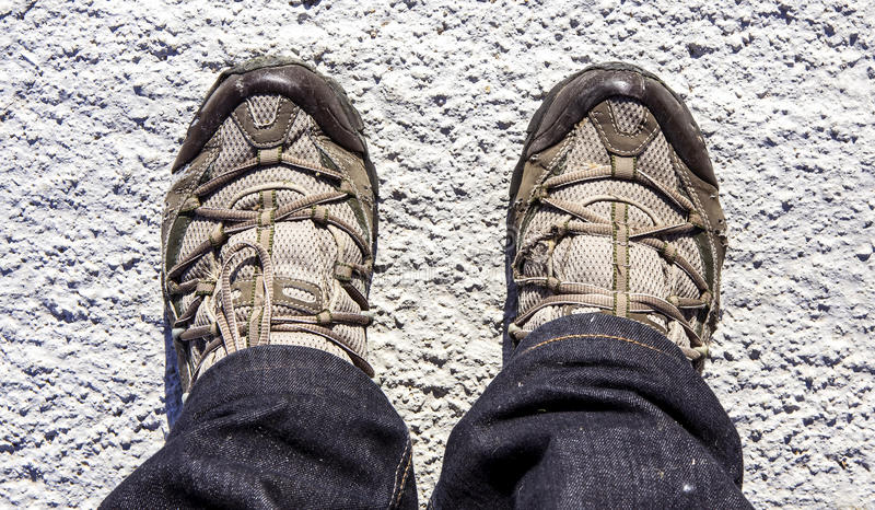 Sports Shoes. A pair of worn out sports shoes and blue jeans stock photos