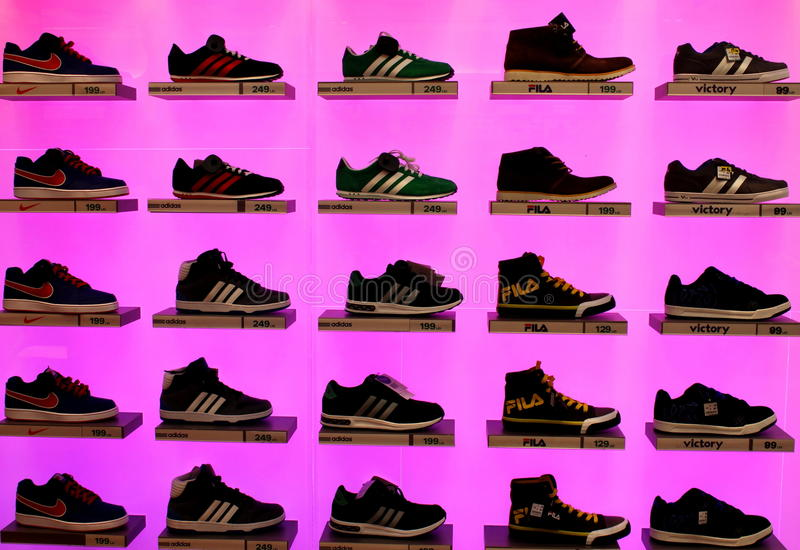 Sports shoes. Shelves with branded sports shoes on pink background stock photo