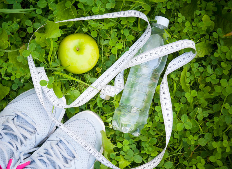 Sports shoes sneakers, bottle of water and apple on fresh green grass royalty free stock photo