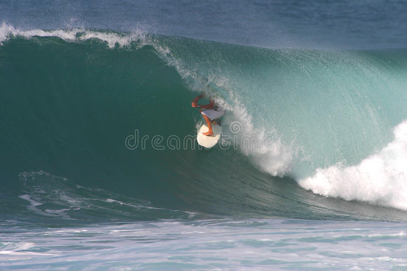 Sports Surfer Surfing. A surfer riding deep in the tube of a wave while surfing at Backdoor surf break in Hawaii stock photography