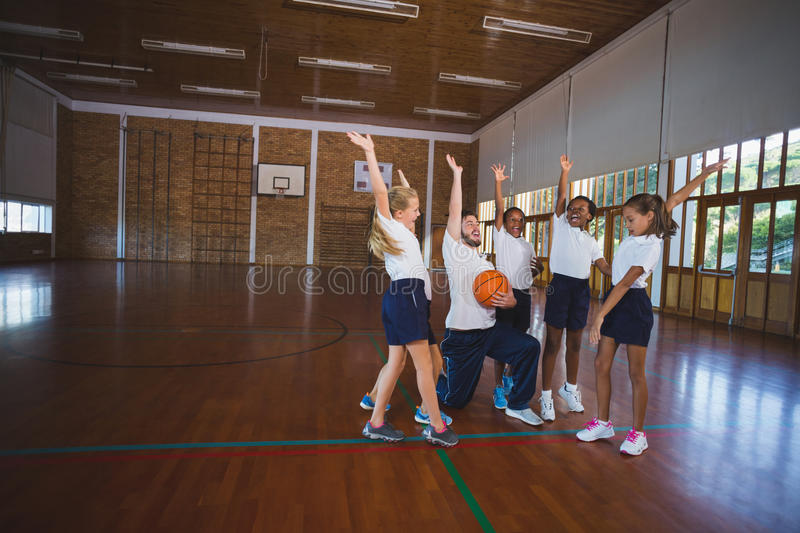 Sports teacher and school kids playing in basketball court. Excited sports teacher and school kids playing in basketball court at school gym royalty free stock photos