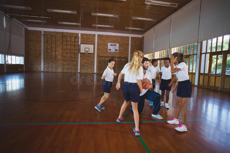 Sports teacher and school kids playing basketball. In court at school gym royalty free stock images