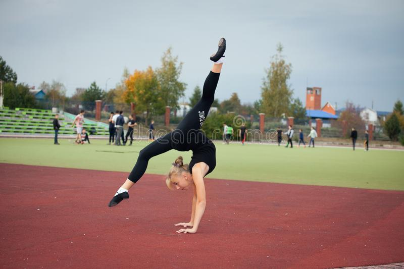 Sports teenage girl in the stadium performs gymnastic exercises stock photo