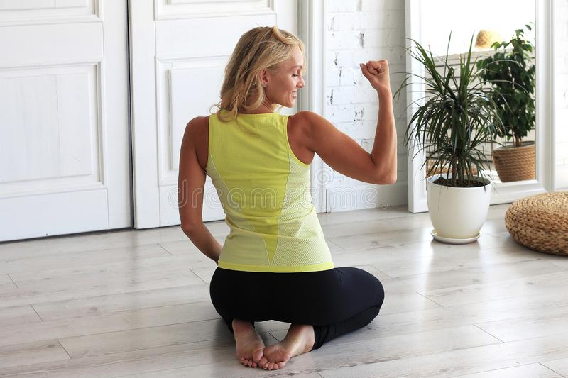 Sports training at home. Full length portrait of attractive woman in sport uniform training out at home in living room, doing yoga stock image