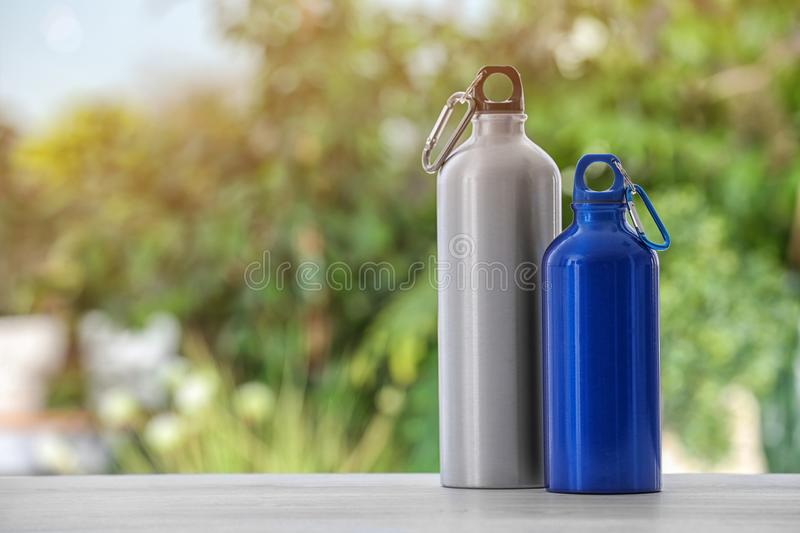 Sports water bottles on table against blurred background. Space for text royalty free stock photo