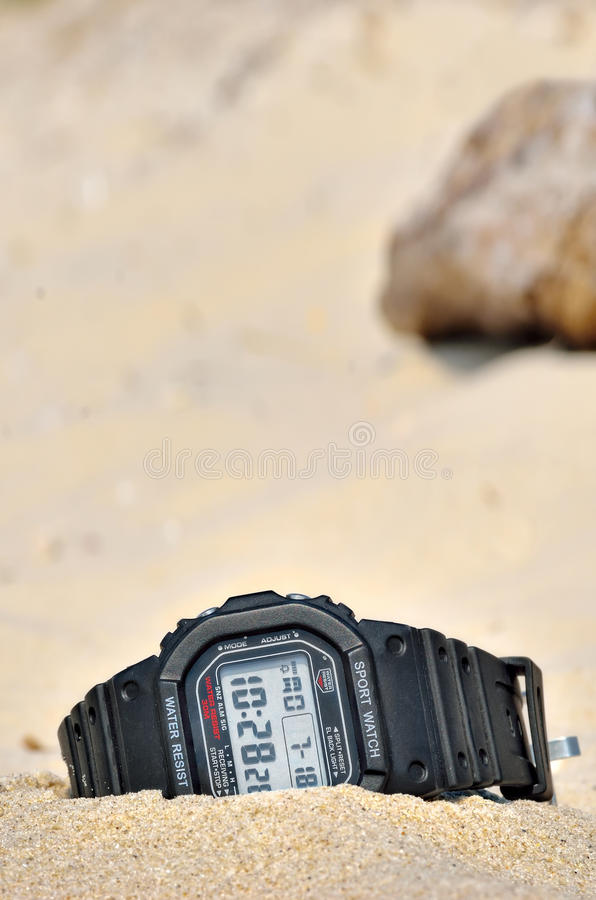 Sports waterproof watch forgotten in the sand. royalty free stock photography