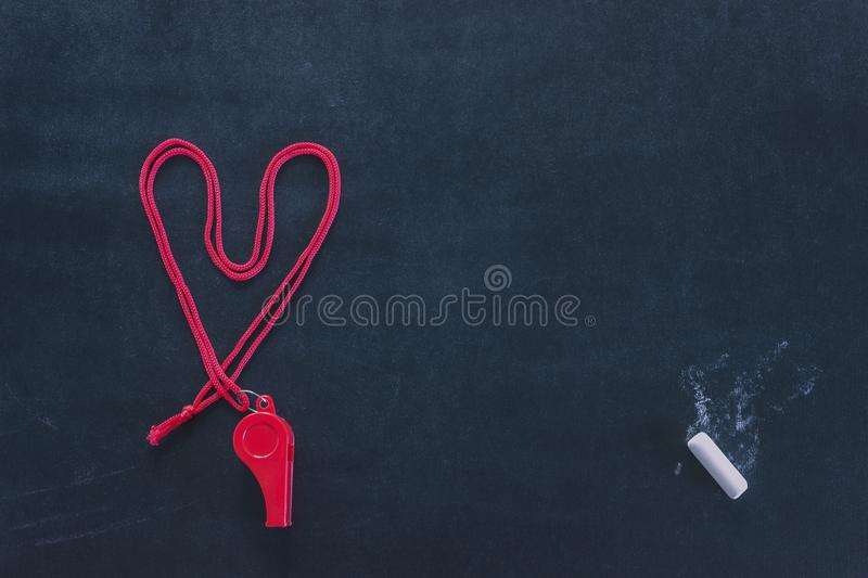 Sports whistle on a red lace. Laid out in the shape of a heart. Piece of white chalk. Concept- sport competition, referee, statis royalty free stock photo