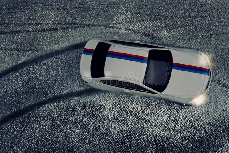 A sports white car with a blue and red stripe drifts and leaves a tire imprint on the asphalt. royalty free stock images