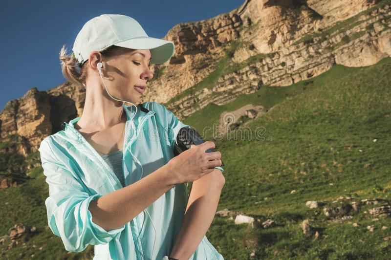 A sports woman in a cap and nuzhniki switches the songs to her mobile phone during an outdoor exercise against the. Background of fields and rocks stock images