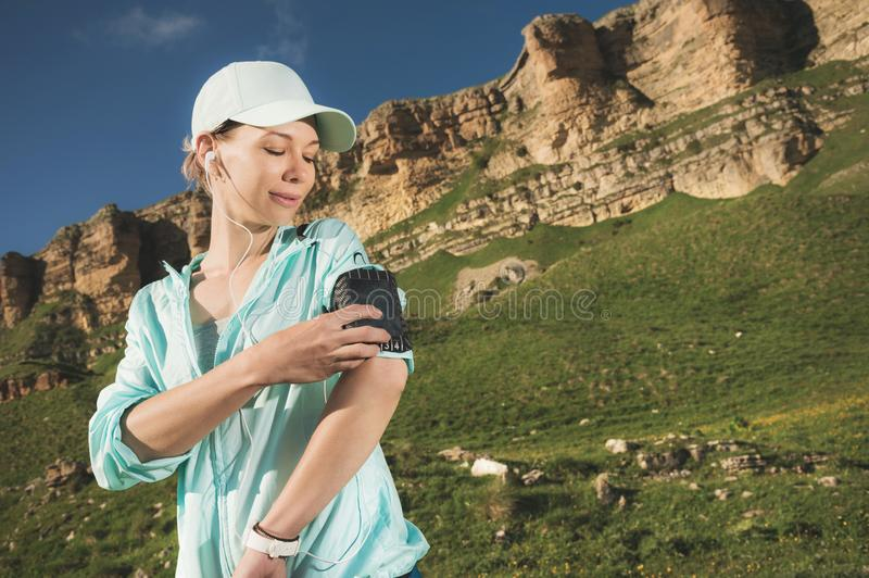 A sports woman in a cap and nuzhniki switches the songs to her mobile phone during an outdoor exercise against the. Background of fields and rocks stock image