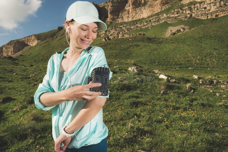 A sports woman in a cap and nuzhniki switches the songs to her mobile phone during an outdoor exercise against the. Background of fields and rocks royalty free stock photo