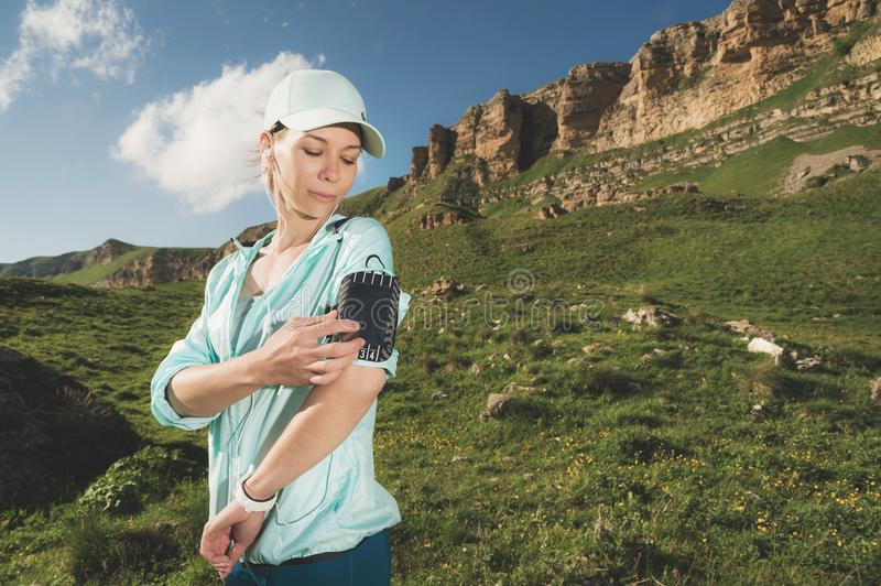 A sports woman in a cap and nuzhniki switches the songs to her mobile phone during an outdoor exercise against the. Background of fields and rocks royalty free stock photos