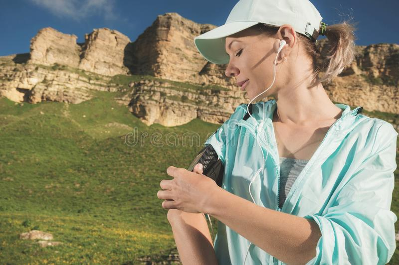 A sports woman in a cap and nuzhniki switches the songs to her mobile phone during an outdoor exercise against the. Background of fields and rocks royalty free stock images