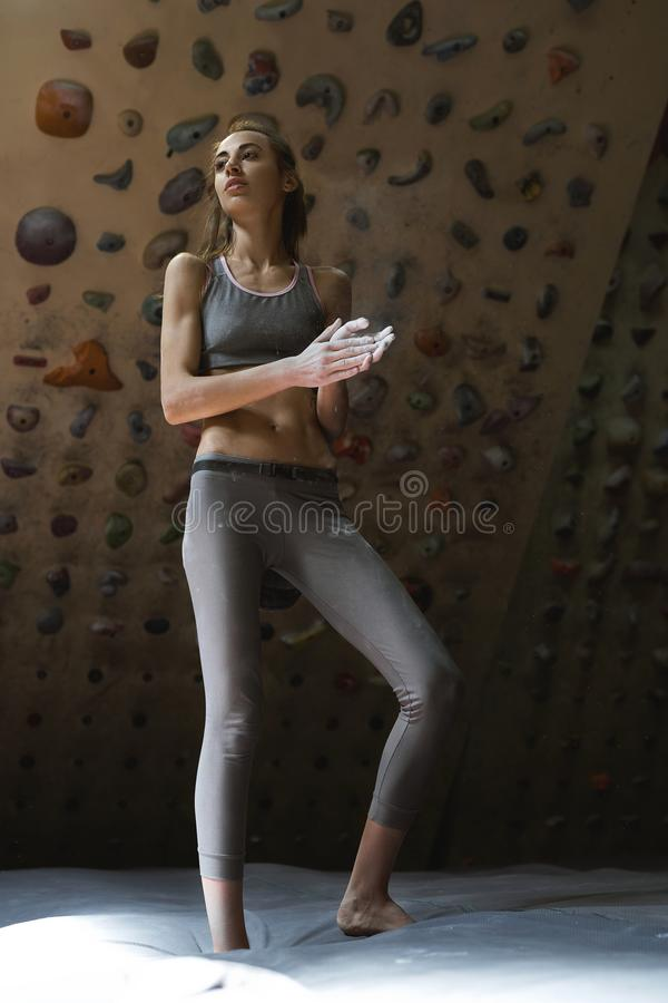 Sports woman climber is chalking hands with white chalk powder before climb in indoor climbing gym. woman getting ready. To climbing. exercising and training in stock photography