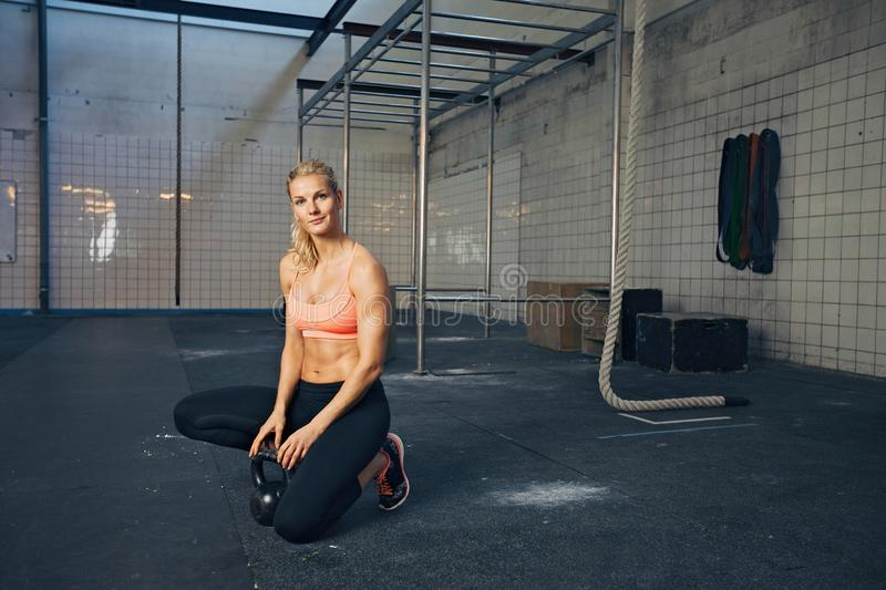 Sports woman at crossfit gym with kettlebell. Beautiful young woman with kettle bell looking at camera. Fit caucasian female athlete at crossfit gym relaxing on stock photography