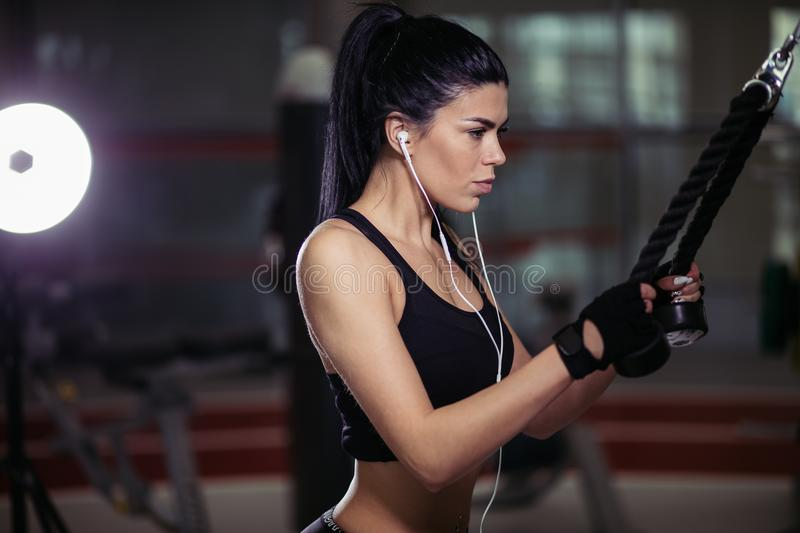 Woman doing exercise at crossover machine in gym royalty free stock photos