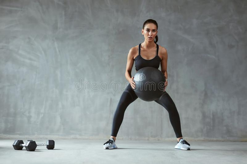 Sports Woman In Fashion Sportswear Squats With Fitness Ball. Female In Black Sport Clothes. High Resolution stock photos