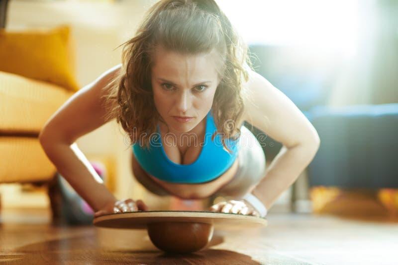Sports woman in modern house doing pushups using balance board royalty free stock photo