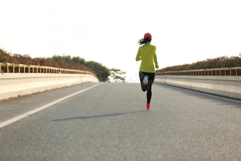 Sports woman runner running on city road. Young sports woman runner running on city road stock image