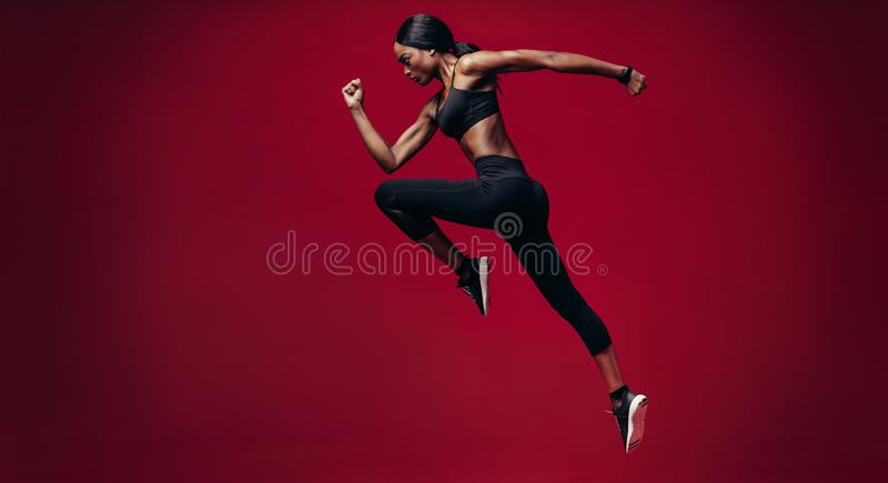 Sports woman running over red background stock photos