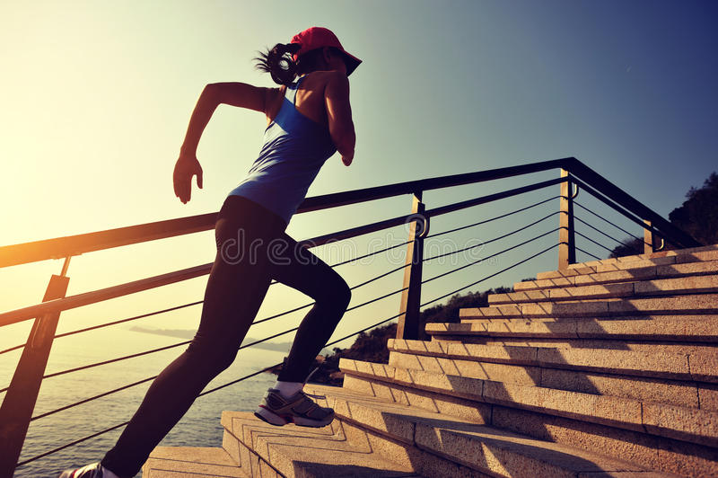 Sports woman running up on stairs sunrise seaside stock image