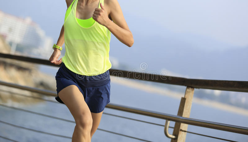 Sports woman running on wooden boardwalk seaside. Fitness sports woman running on wooden boardwalk seaside royalty free stock photo