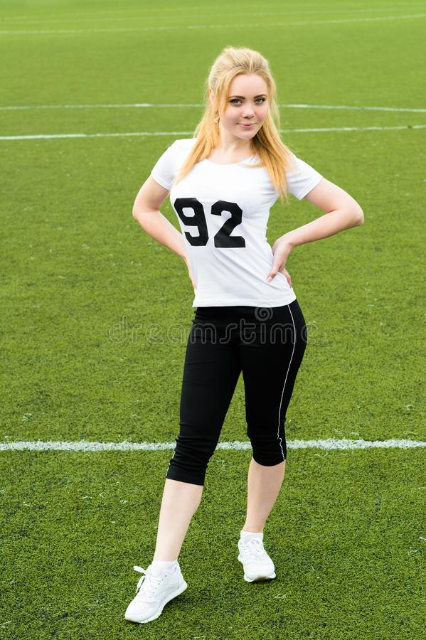 Sports woman standing full length on green grass football field royalty free stock photo